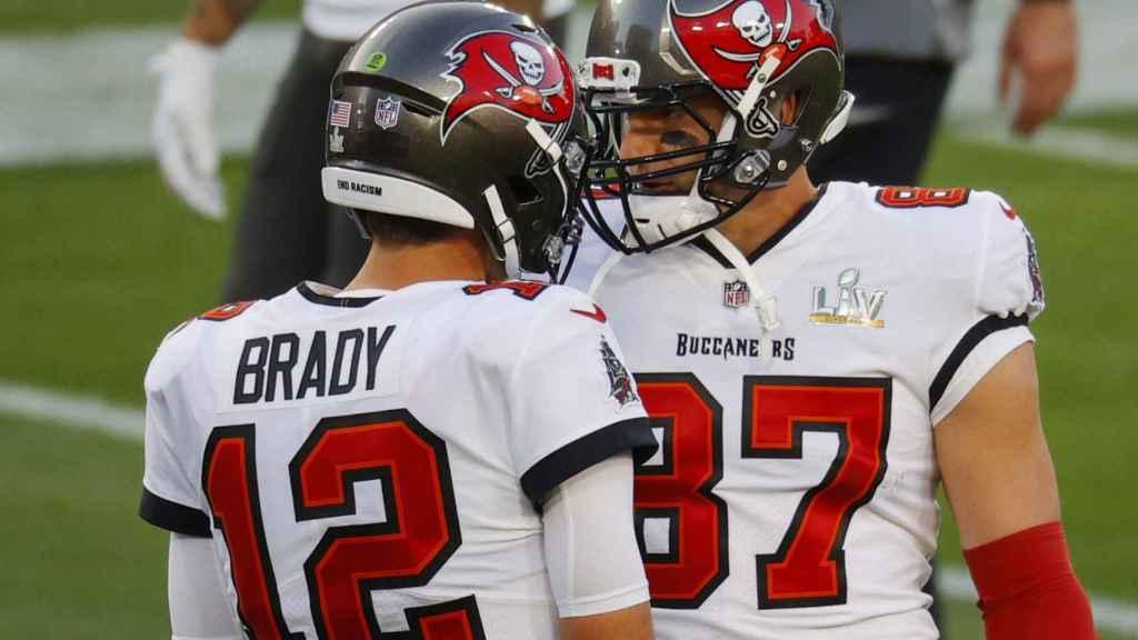 Tom Brady y Rob Gronkowski chocan sus cascos durante el partido