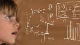 Una niña observa una pizarra digital con operaciones matemáticas.
