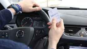 Un conductor sujeta su carné de conducir.
