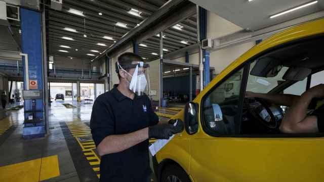 Un trabajador de una estación de ITV de Madrid da las indicaciones desde fuera del coche a un conductora.