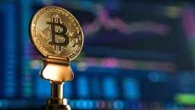 Una moneda de bitcoin sobre unas gráficas de cotización.