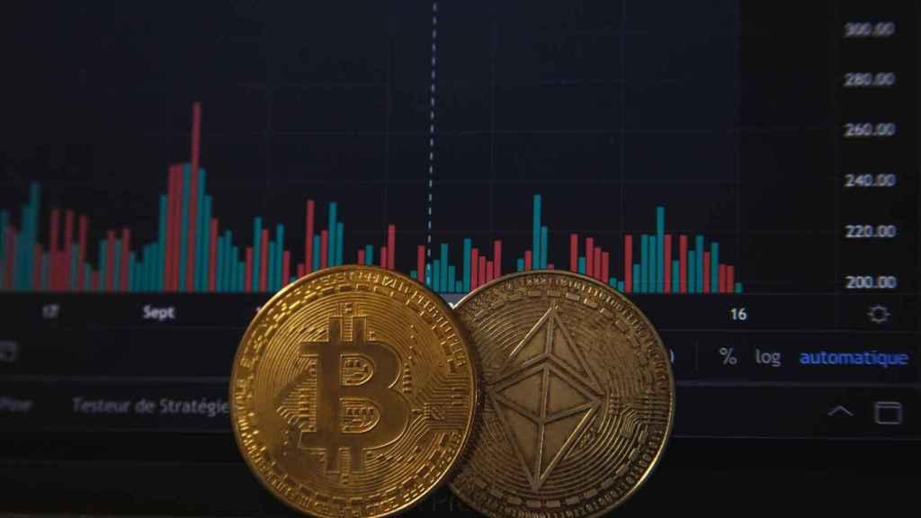 Monedas de bitcoin y ethereum sobre gráficas de cotización.