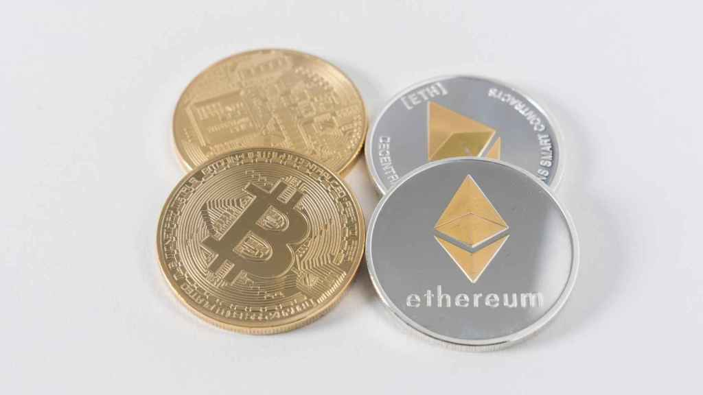 Monedas físicas con los símbolos del bitcoin y el ethereum.