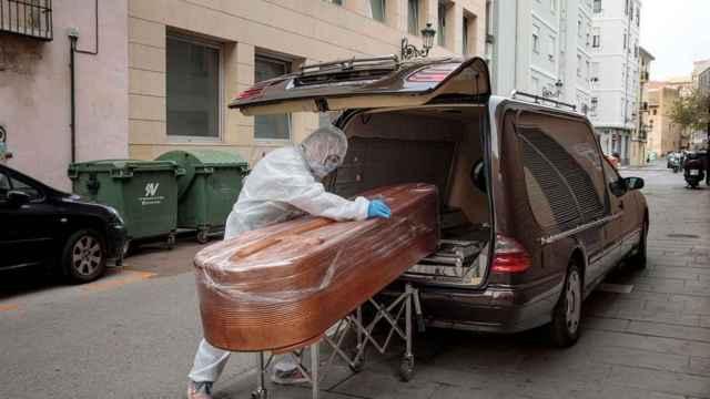 Un funerario metiendo un ataúd en un coche.