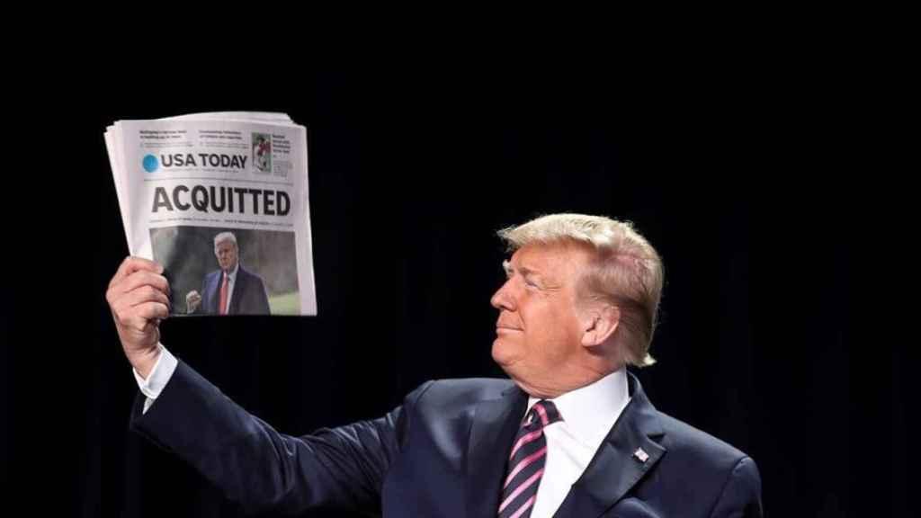 Donald Trump sostiene un ejemplar del periódico USA Today con la palabra absuelto.