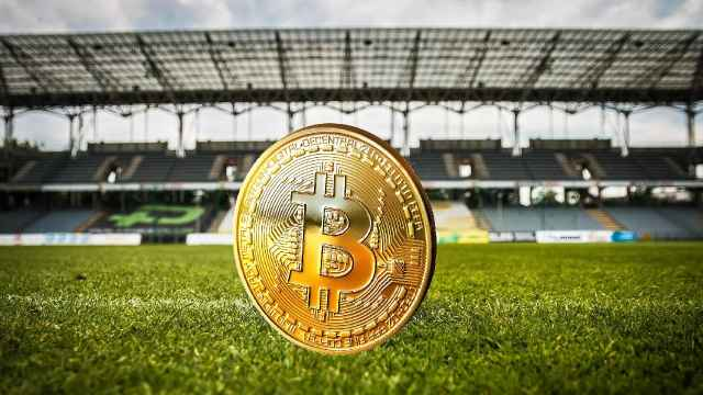 Una moneda de bitcoin en un campo de fútbol.