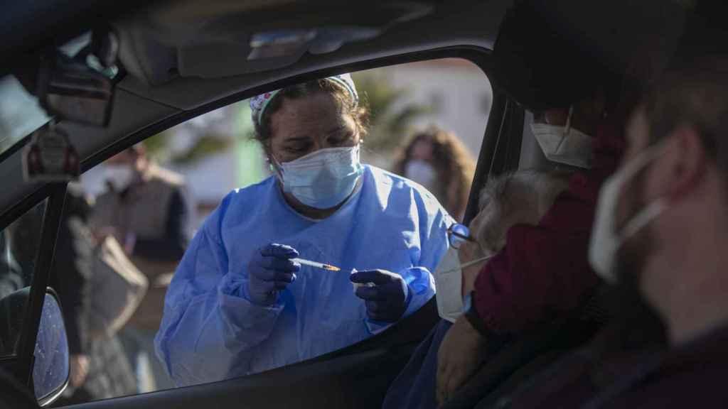 Una mujer mayor de 90 años recibe desde el coche la vacuna de Pfizer contra la Covid-19, en una carpa habilitada en la explanada del centro de salud del municipio Lora del Río. (María José López / EP)