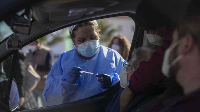 Una mujer mayor de 90 años recibe desde el coche la vacuna de Pfizer contra la Covid-19, en una carpa habilitada en la explanada del centro de salud del municipio Lora del Río.
