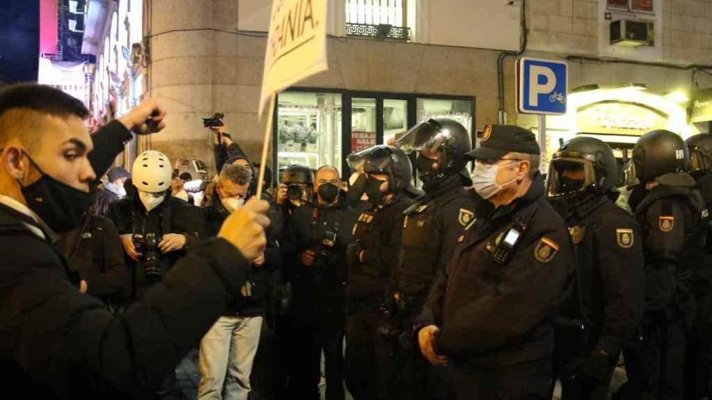 Imagen de un manifestante en frente de la un agente de la Policía Nacional.
