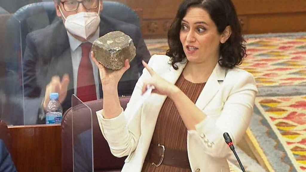 Isabel Díaz Ayuso se lleva un adoquín de la calle a la Asamblea de Madrid.