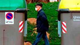 Un hombre camina entre dos contenedores de basura.