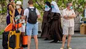 Turistas en Sevilla mientras dos hermanas de la Cruz pasan por detrás con mascarillas.