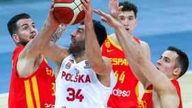 Tres jugadores de España defendiendo ante el ataque de Polonia