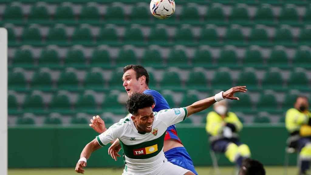 Kike García pelea un balón contra la defensa del Elche