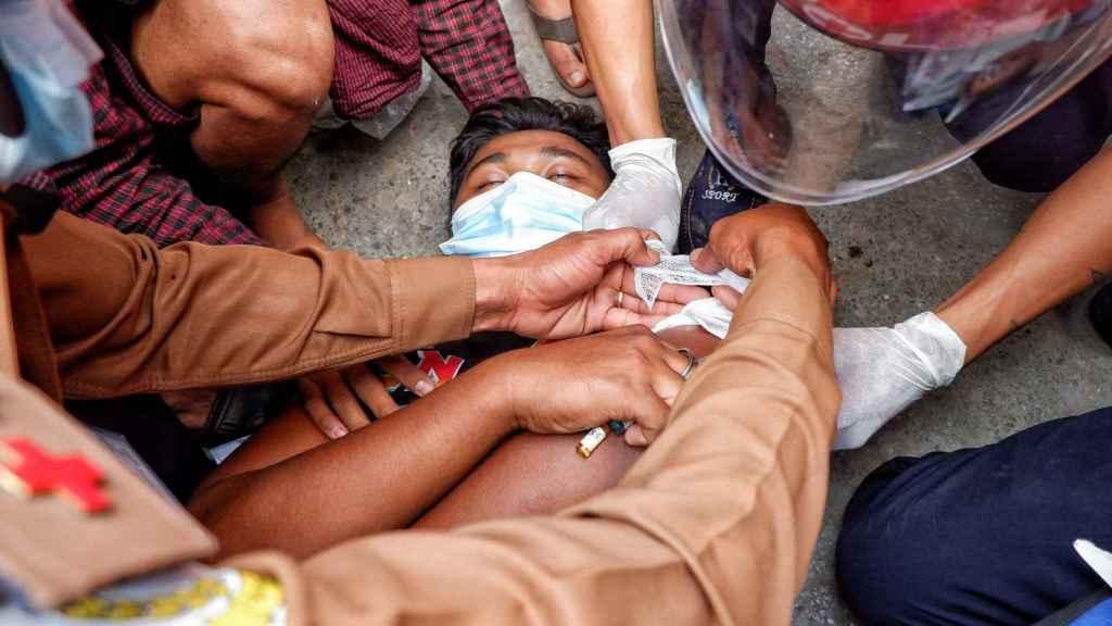 Un hombre en el suelo herido en una de las protestas en Mandalay, Birmania.
