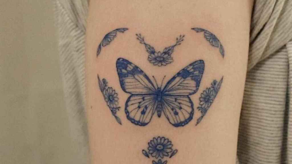 Butterfly tattooed on the upper arm.