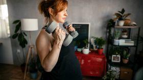 Una mujer embarazada, haciendo un ejercicio de fuerza.