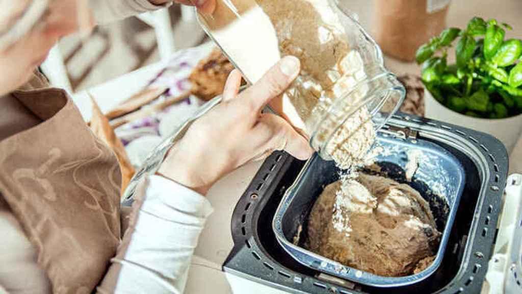 Una persona echa los ingredientes en su panificadora para elaborar pan casero.