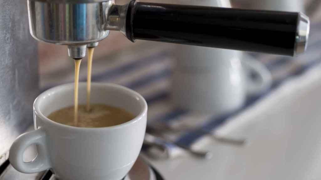 Una cafetera eléctrica echando el café en una taza.