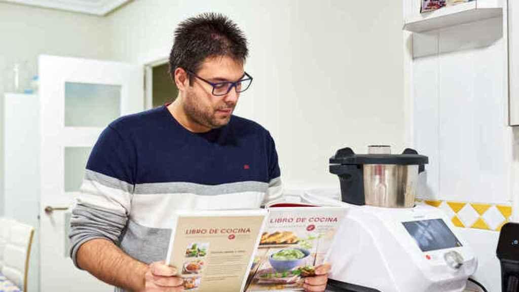 Un usuario leyendo un libro de recetas para su robot de cocina.