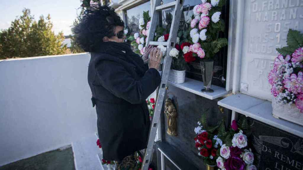 Sofía Benítez-Cubero putting flowers to her aunt Antonia Reguera, the person who raised her, in the El Coronil cemetery (Seville).