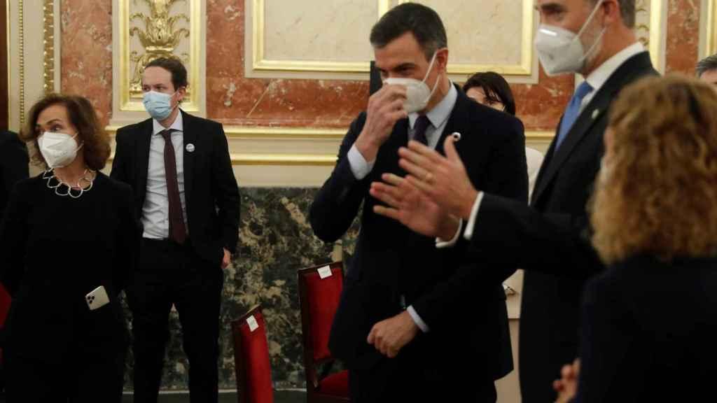 El Rey Felipe VI, entre Pedro Sánchez y Meritxell Batet, junto a Carmen Calvo y, de fondo, Pablo Iglesias con las manos en los bolsillos.