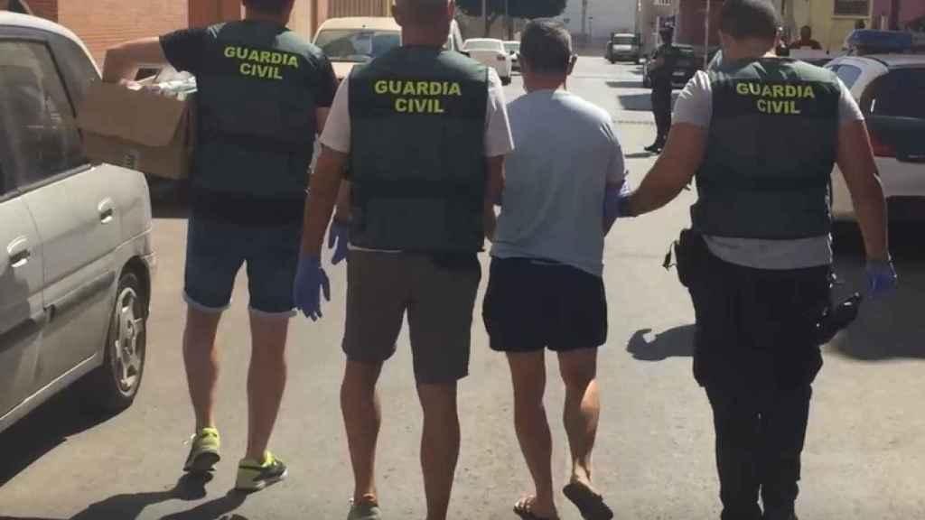 Agentes de la Unidad Orgánica de Policía Judicial custodiando a uno de los detenidos.