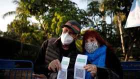 Dos ciudadanos israelíes muestran su 'pase verde', un certificado de vacunación.