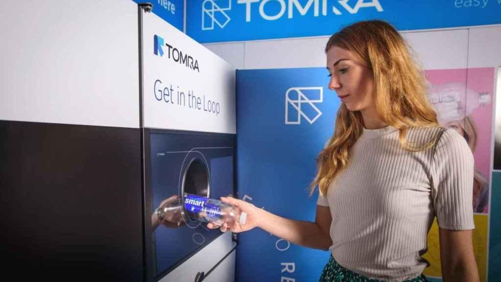 Una mujer deposita una botella en una máquina de Tomra, la multinacional noruega que financia un lobby ecologista en España.