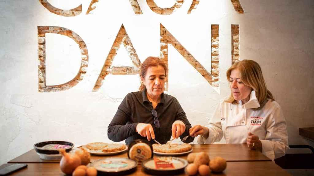 La cocinera experta en tortillas de patata, Teresa Cuerda, cortando una de las tortillas probadas mientras Lola observa.