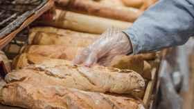 Una persona toma una barra de pan con un guante.