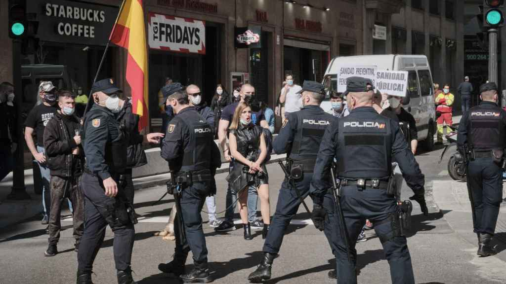 Varios agentes ante un grupo de extrema derecha en una manifestación por la Sanidad Pública.