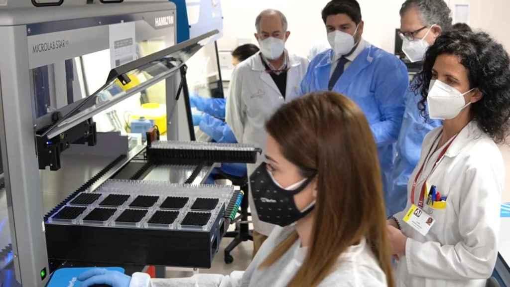 Personal del laboratorio de La Arrixaca mostrando al presidente de la Región de Murcia cómo funciona el nuevo robot.