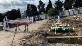 Un sacerdote oficia un responso en el cementerio de Alto de São João, el mayor de Portugal.