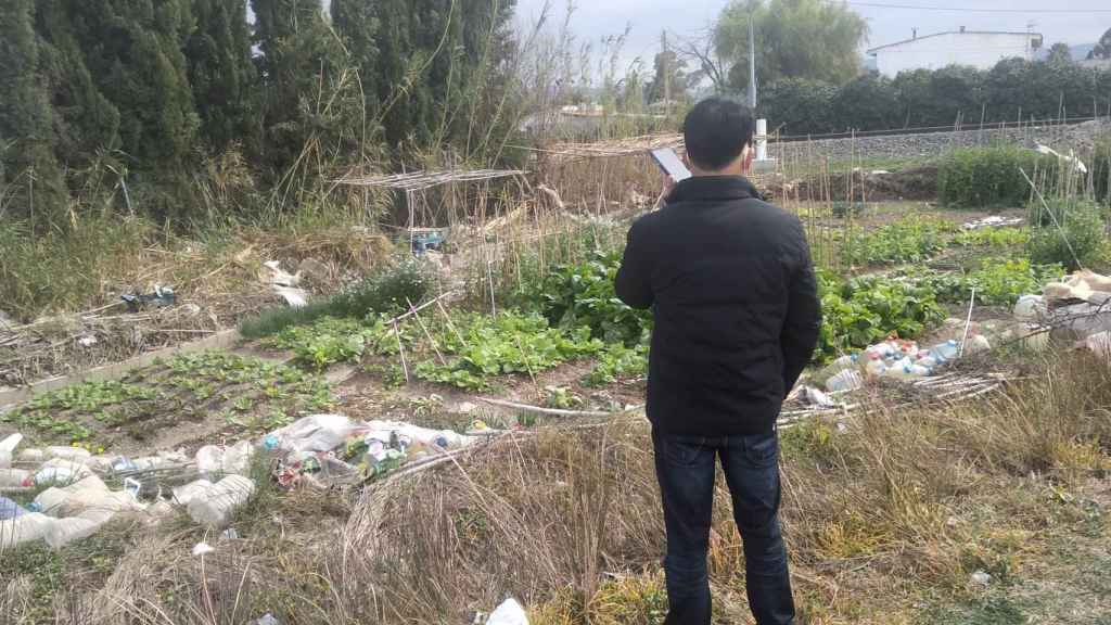Uno de los comerciantes chinos supervisando la producción del 'huerto okupa'.