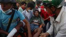 Varios manifestantes trasladan a un herido en las protestas.