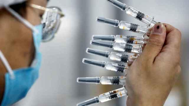 Un trabajador de Sinovac con viales de la vacuna.