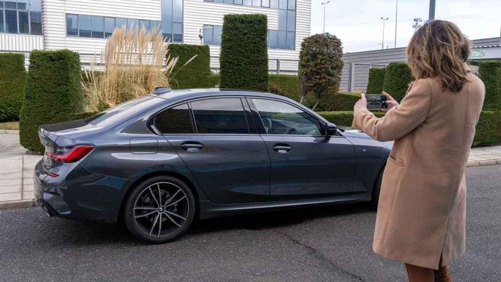 Una mujer toma fotos de un coche con su teléfono móvil.