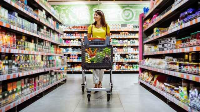 Una mujer recorre el supermercado con un carrito.