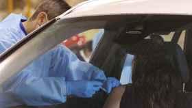 Un sanitario inocula una dosis a una mujer en la primera jornada de vacunación masiva en Málaga.