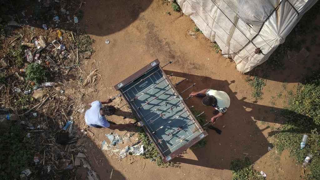 Los inmigrantes han instalado un pequeño futbolín en el campamento de Lepe (Huelva).