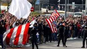 Seguidores del Atlético de Madrid y fuerte presencia policial en los alrededores del estadio Wanda Metropolitano en Madrid este domingo, antes del derbi liguero entre el Atlético de Madrid y el Real Madrid