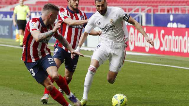 Karim Benzema perseguido por dos jugadores del Atlético de Madrid