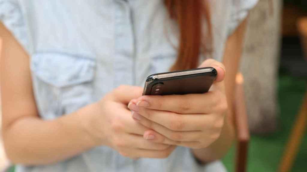Una joven contempla una aplicación en su smartphone.
