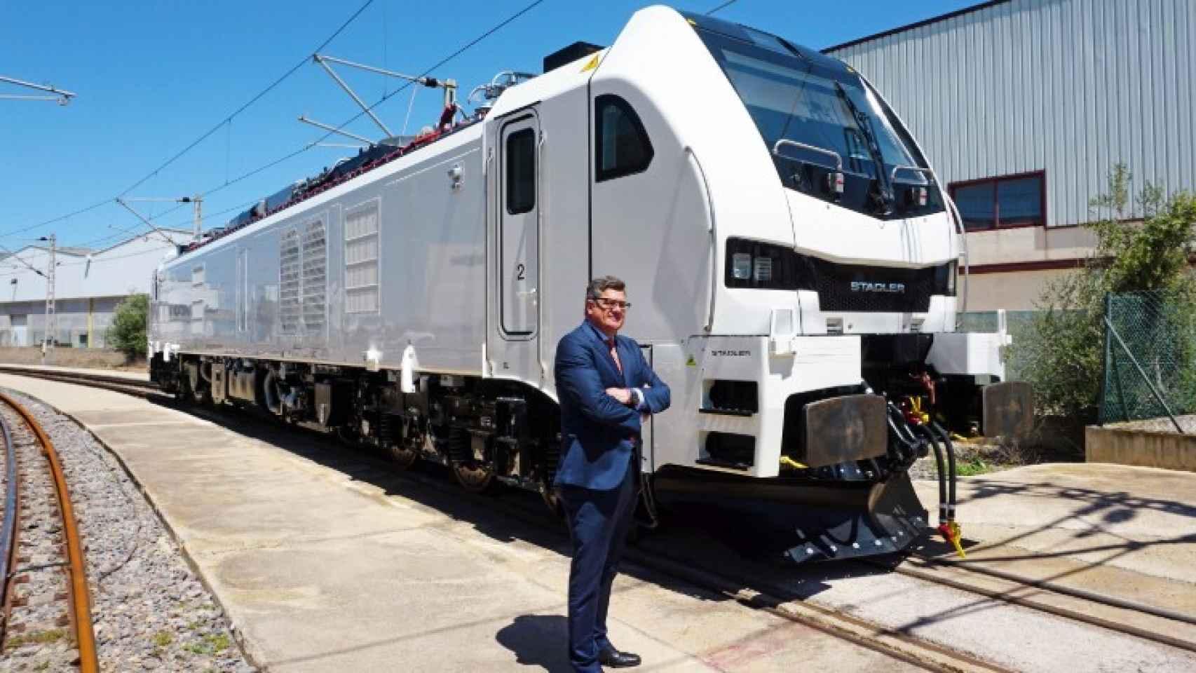 Íñigo Parra, presidente de Stadler Valencia, junto a una locomotora producida en la factoría. EE