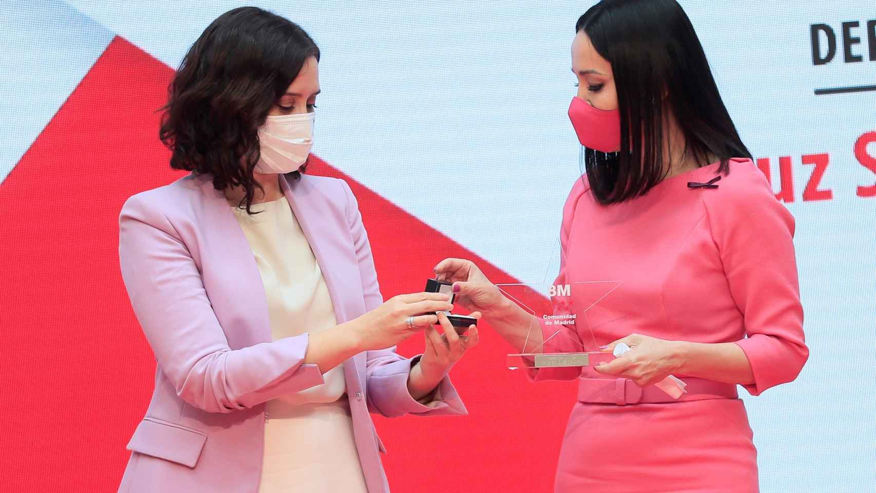 La presidenta de la Comunidad de Madrid, Isabel Díaz Ayuso (i), entrega un galardón a la abogada Cruz Sánchez de Lara, en la categoría de Derechos Humanos durante la entrega de los Reconocimientos 8 de Marzo que, con motivo del Día Internacional de la Mujer, otorga este lunes el Gobierno regional.