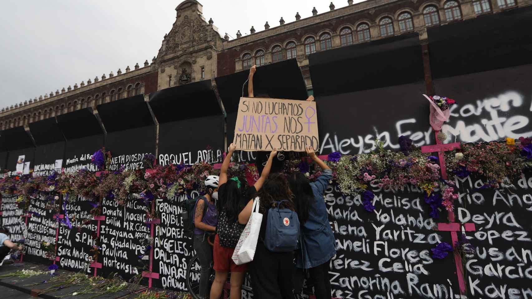 Mujeres colocan flores y carteles en la valla frente al Palacio Nacional de México.