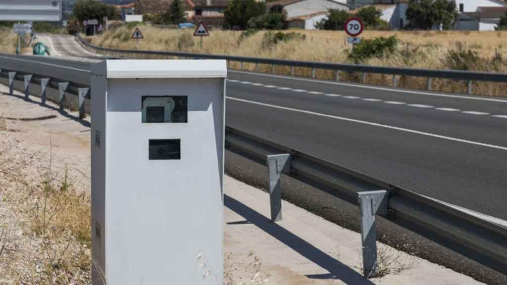 Un coche, en un autovía, pasando al lado de un radar de velocidad de la DGT.