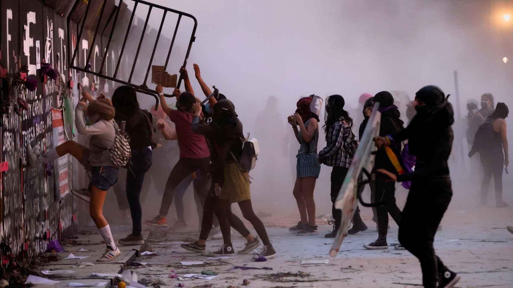 Manifestantes del 8-M en Ciudad de México tratan de acceder al Palacio Nacional.