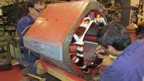 Dos técnicos de Motorlan reparando una pieza de un motor eléctrico industrial en su planta.